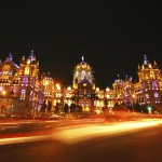 Mumbai's CST (Chatrapati Shivaji Terminus) illuminated at night with streaks of vehicular traffic headlights in foreground and copy space